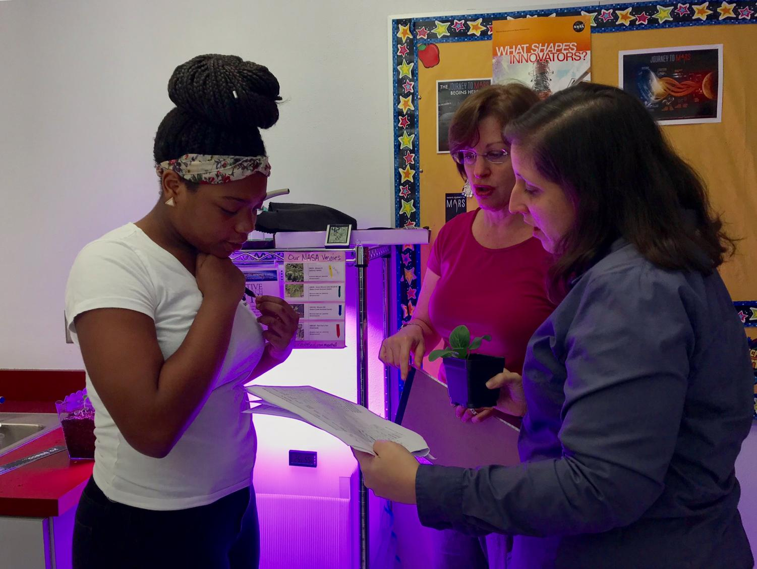 Student Aiyana Lespinasse (left), evaluator Catherine Raymond (middle), and science teacher Amy Leonard (right) speak about the growth of plant #7 which has grown over eight centimeters.