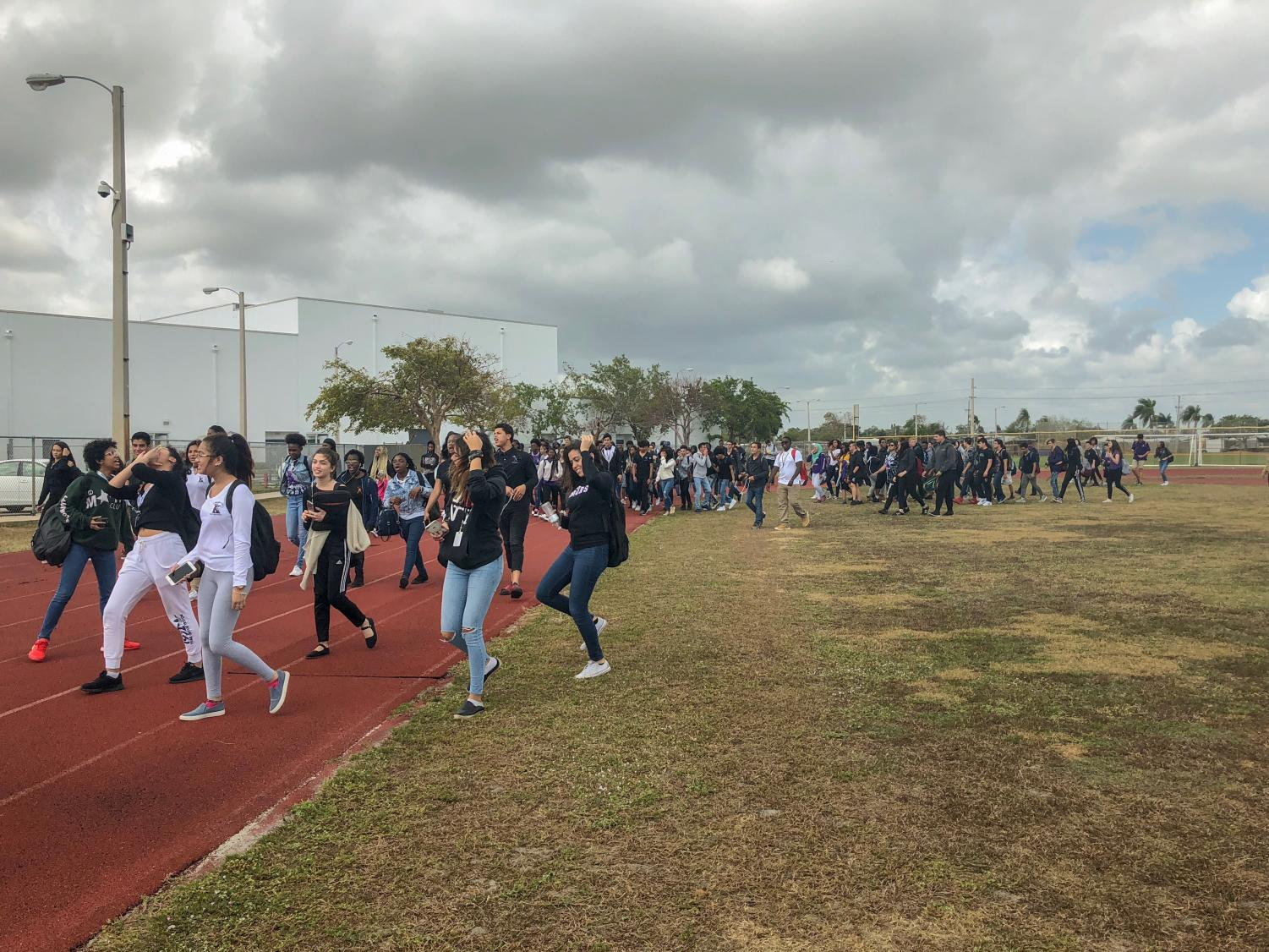 Students walk the track in support of gun control reform as a part of the