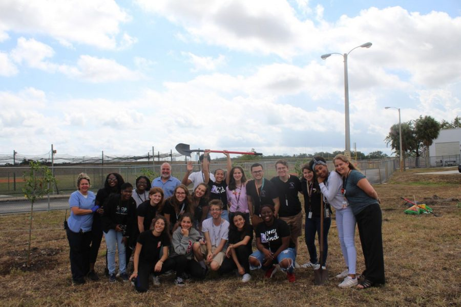Students+take+group+photo+with+staff+after+planting+17+Trees