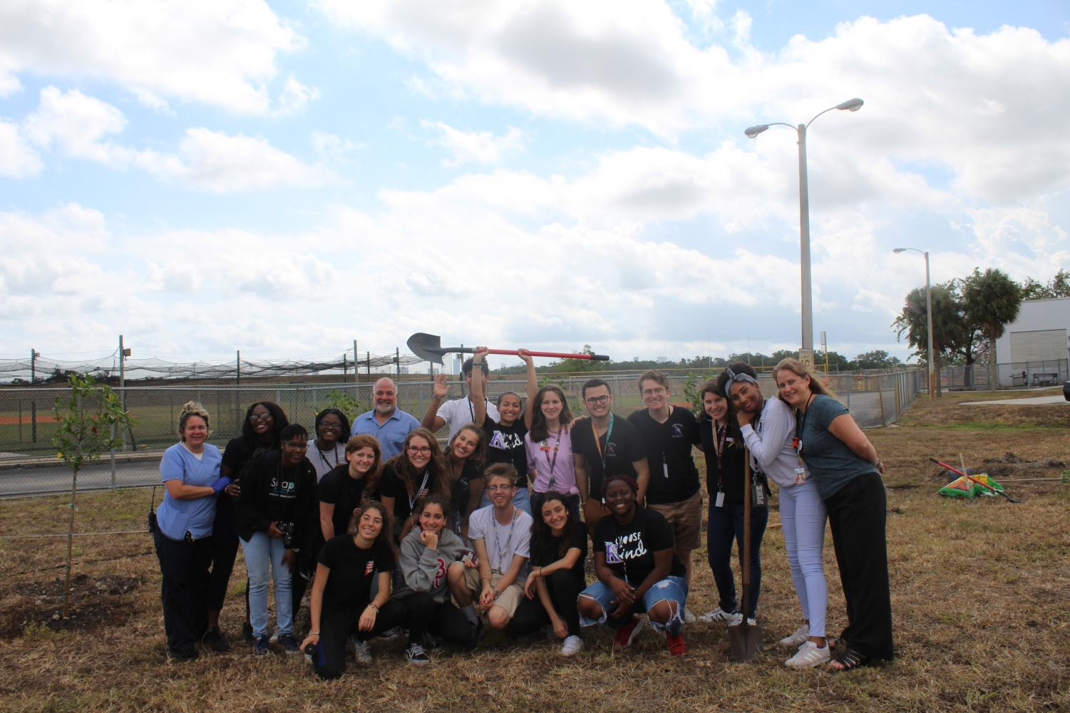 Students take group photo with staff after planting 17 Trees