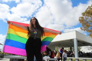 Student Keren Yehezkely holds a rainbow flag on Diversity Day to represent support for the LGBTQ+ community
